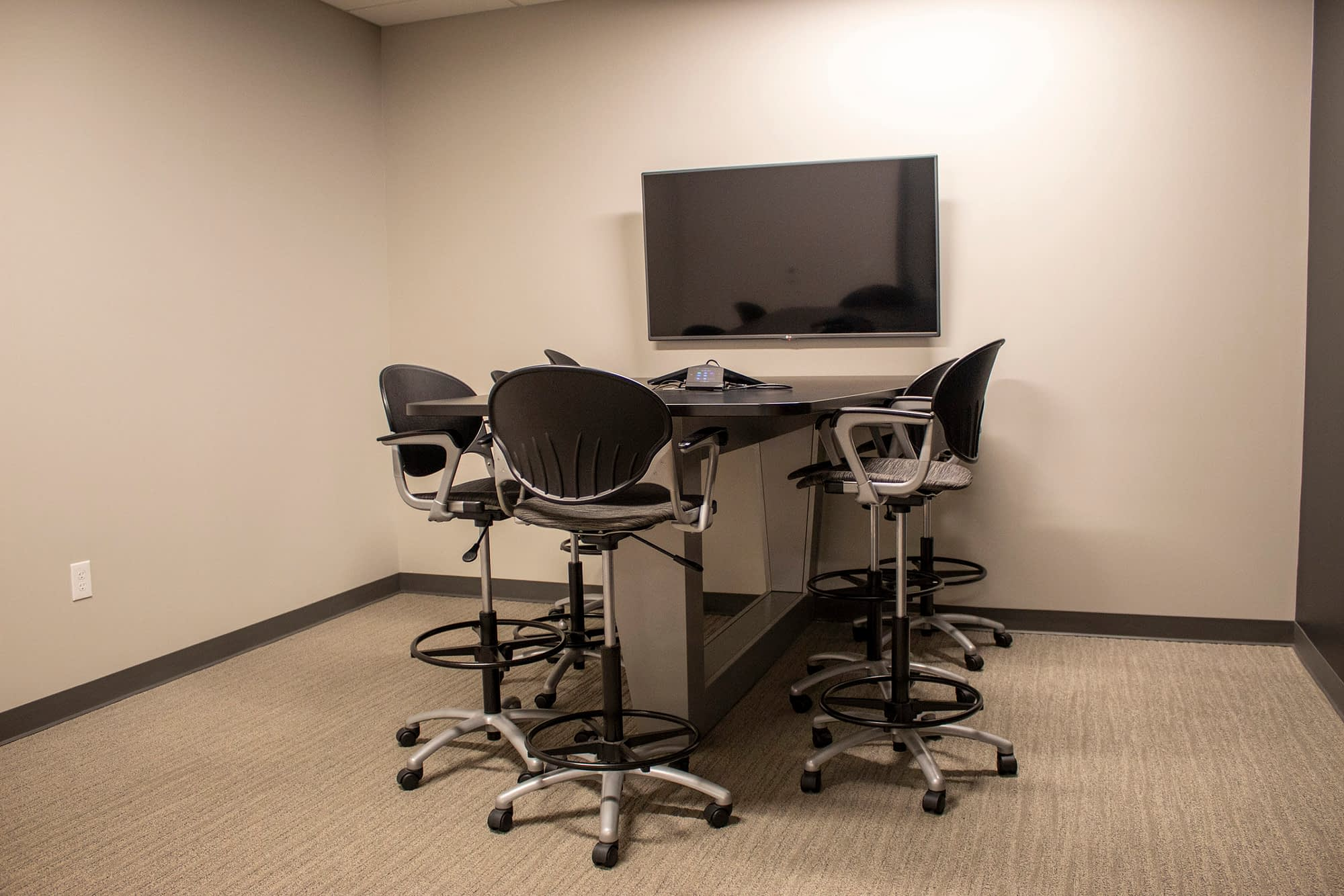 small conference room with standing height table and chairs and media center